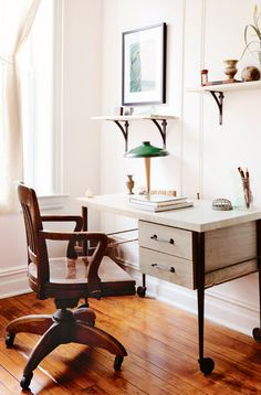 White desk with wood chair and small green lamp