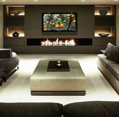 Modern den or living room area. Sectional sofa with fireplace and backlit shelves. Flat screen with grey or dark on light color scheme. Found at ig_interiors on instagram.