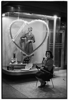 Henri Cartier-Bresson. 1963. Havana. Militia woman guards a ladies fashion store, which advertises for Valentine's Day business
