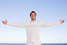 Happy young guy stretching his arms at beach Royalty Free Stock Photo