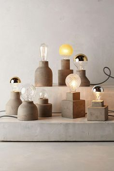 Waxed concrete Paved pedestal lamp bases -- and nice assortment of bulbs. www.anthropologie.com