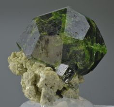 Demantoid, Soghan, Baft County, Kerman Province, Iran. Size 19 x 18 x 15mm. A choice thumbnail of a perfect 360 degree deep green Garnet nicely perched on a small matrix along with a smaller Demantoid