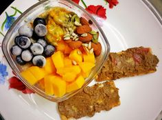 Early morning brekkie. Vanilla Oatmeal topped w mangoes,  frozen blueberries,  passion fruit,  almonds, pumpkin seeds and sunflower seeds. Along w guac on 2 multigrain crispbread :)
