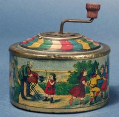 Tin Hand Cranked Music Box Penny Toy ca. 1900 Germany Very early, crank activated music box dating from around 1900 and beautifully illustrated with images of an idyllic Victorian childhood. It shows