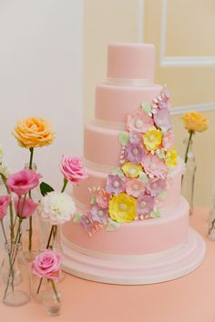 Pink wedding cake with purple and yellow flowers