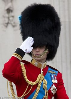 Prince William raises his hand in salute while riding alongside Princess Anne during the Trooping of the Colour parade today