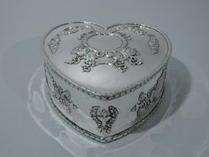 Only one in stock of this item shown. Regal Sterling Silver Heart Box by Howard 1897 Contact: 646-863-5416 Sterling silver heart box. Made by Howard in New York in 1897. Heart form with hinged cover. Ornament includes garlands and ribbon applied to sides and cover. Also, three cartouches (vacant) with regal crowns. Hallmark includes date and model no. 166. Call For More Info. #SterlingSilverHeartBox #SilverAnniversaryGift #AntiqueHeartBoxes #SterlingSilverHeartShapedBox #SilverWeddingGifts