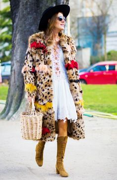 Anna Dello Russo wears a lacy white dress, leopard coat, basket bag, felt hat, and lace-up suede boots