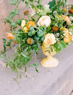 rustic wedding centerpiece - pale yellow and peach garden roses, orange ranunculus, yellow cockscomb, and rust colored coneflowers provide cheerful color to this riot of greens: jasmine, mint, figs, scented geranium, and fuzzy almonds make up the centerpiece.