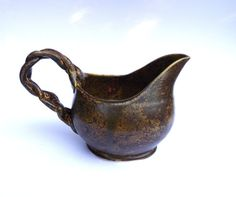 """Hand Made Ceramic Stoneware Gravy Boat by SarahWhyteArtwork on etsy This is a dark brown large stoneware gravy boat. It is 5"""" tall and 8"""" wide, and holds about 17oz. It would be perfect for family gatherings. This piece was thrown on the wheel, and then the top was cut away to form the exaggerated spout. A handle was braided and added and it was fired."""