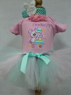 Personalized Baby Girl Easter outfit. This outfit includes an adorable light pink onesie featuring a cute Easter Bunny peeking around a number one. It says 1st Easter. You may add your child's name to the onesie. The tutu is very pretty in soft colors of pale aqua blue, pale pink and white tulle. It has a ribbon tie waist band but you can ask for an elastic waist if you prefer. The onesie has three pretty pink shabby flowers at the neck and the headband features an adorable rosette white…