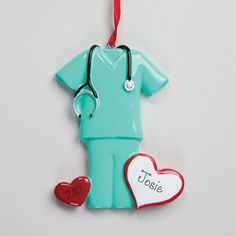 """Green Scrubs Ornament, Personalized Dedicated to the big-hearted professionals who devote their careers to helping others. Green Scrubs Ornament is personalized with up to 8 characters on the white heart, 4 characters on the red heart. 3""""W x 3-3/4""""H x 1/4""""D"""