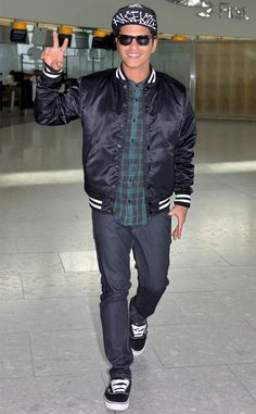 Oh hey there, Bruno Mars! The super cool singer, in classy wayfarer sunnies, flashed the peace sign to fans at a London airport!
