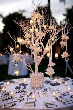 A closer look at the gorgeous seating card table with a white tree and hanging candles floral