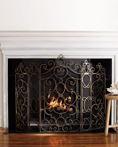 "Fireplace screen inspired by the fanciful form of Parisian balcony railings. Handcrafted iron; antiqued brass finish 57.25""W x .25'D x 41""T. Imported."
