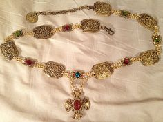 Renaissance chain of office or livery collar by Karen Troeh with red, blue, purple and green rhinestones, antique gold filigree links, and a large equal-armed cross vintage pendant with shield decorations. This one is sold, but visit my Etsy shop for more chains of office or to order a custom design for yourself!
