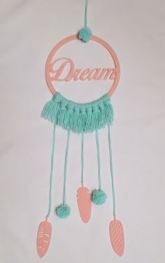 Light pink laser cut acrylic Dream catcher and feathers with mint green/light aqua blue yarn tassels and pompoms.  wall hanging decoration