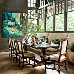 Rugged Sophistication | A handsome trestle table enhances the rustic elegance of the dining room in this cabin-inspired lake house. With the long banquette and plenty of upholstered chairs, there's room enough to host a crowd, but it still feels cozy enough for a quiet meal for two.