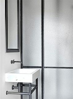 Nicolas Schuybroek, white marble sink. Steel frame shower screen. Black electroplated wall mounted tap basin mixer.