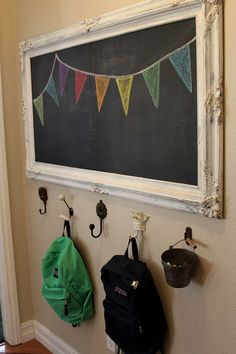 Chalkboard with beautiful painted frame salvaged from the garbage.  Wall hooks strong and well-anchored enough to hold backpacks.