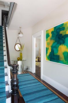 The interior of 21 Broad Hotel epitomizes a modern coastal vibe perfect for its Nantucket, Mass., setting. A vivid blue, green and yellow abstract acrylic-on-wood painting perfectly complements the blue rug and matching stair runner.