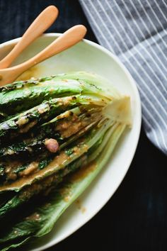Grilled Greens Salad with Anchovy Vinaigrette - Not Without Salt  Ingredients:  1 head romaine, halved lengthwise 2 tablespoons olive oil Anchovy vinaigrette (see recipe below) 1 cup halved cherry tomatoes (optional)  Anchovy Vinaigrette 2 tablespoons red wine vinegar 1 teaspoon Dijon mustard 1 small shallot, finely diced 3 anchovy fillets ¼ teaspoon chili flakes ⅓ cup extra-virgin olive oil Salt and pepper