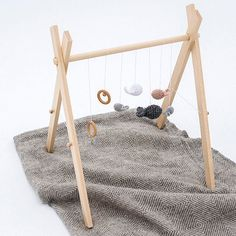 This simple wooden play mobile won't cost much to make and you can add colourful or interesting shapes, homemade toys or eye-catching items to keep your little one occupied.