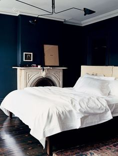 an old fave: Jenna Lyons' bedroom for Domino, black walls, white bed linens, Turkish rug, Serge Mouille pendant, fireplace