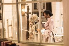 Rebecca James (Mouna Traoré), the night cleaner, dusts a skeleton in the morgue