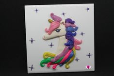 Unicorn Home Décor Ceramic Tile Art Girls Room Décor. My Unicorn home décor is the perfect keepsake gift for that special someone and makes a truly unique gift, one of a kind 3D Wall Art. Sparkles the Unicorn is showing off her good side with heart shaped eyes, pastel colored mane, and sparkling horn. She'll make any girls room décor pop with her unspoken, sparkly style.