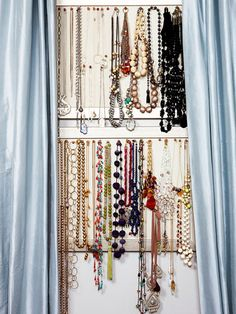 ; hang necklaces on pushpins pushed into framed cork-boards, mounted in-between two windows. Draw curtains and hide the boards. Pull curtains open & see what you have.