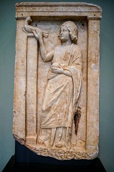 Gravestone of a seven year old Greek girl named Apollonia depicting stroking a dove, the symbol of the soul, and holding a pomegranate, an attribute of Persephone, goddess of the Underworld about 300 BCE | This gravestone is also made in Athens.