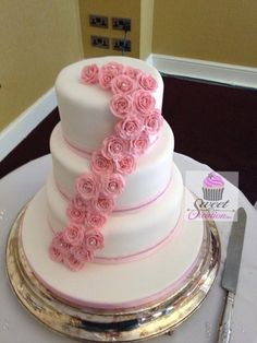 Three Tier Classic white Wedding Cake with cascading Pink Roses