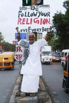 This man has been holding this sign up for over three years to promote religious tolerance in Mumbai.