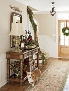 Reindeer and greenery in a tray and a festive bucket filled with pinecones jazz up this hall table. - Traditional Home