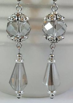 These unique earrings are made with light gray faceted glass crystal beads and pewter beads and bead caps. The antiqued pewter bead caps have a swirl motif. These earrings have a lot of movement and the faceted crystals catch and reflect light beautifully. The earwires on these #pendientes #bisuteria #bisuterias #argentina #pendiente