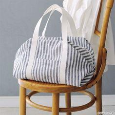 長方形の布を折って縫うだけで作れるキャラメル包みのようなボストンバッグ。サイドから見るとストライプの向きに変化ができて、アクセントになります。 Gift Bags, Handicraft, Bassinet, Gym Bag, Diy And Crafts, Sewing Projects, Pouch, Throw Pillows, Stitch