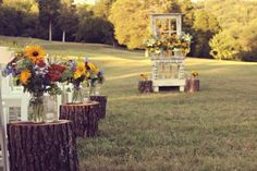 Creative Way to Line the Wedding Ceremony Aisle - Tree Trunks, Florals and a Beautiful Alter!