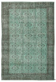 """For a contemporary look with abstract appeal, this green over-dyed rug is skillfully crafted by the revitalization of a genuinehand knotted vintage Turkish rug wovenin the 60'sor 70's. Made from wool on cotton, this """"distressed"""" rug measures 190 cm x 280 cm. The process in creating these works of art begins by shearing to lower the pile and to help """"distress"""" them. They then undergo a series of processes to remove the color. They are now ready to be dyed in one color, a stage that can be…"""