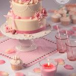 White cake with pink roses and ribbons