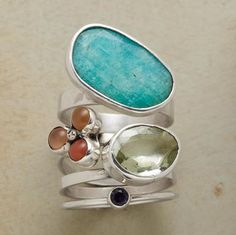 ECLECTIC QUARTET RINGS, SET OF 4--Diverse cut and color—tabletop amazonite, orange moonstone, faceted green amethyst and faceted iolite—unified by sterling silver bands of varying widths.