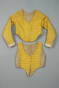 Yellow moire faille brocaded with a repeat of white floral devices, short collarless jacket with open neck, curved hemline, sleeve trimmed with pleated silk ribbon, pieced 2-tone linen lining and boned front placket with hidden eyelets for laces. Vest having silk yoke and pointed front with center stays, tan linen sides and back with laces. Both pieces B-36, L-18. (Jacket small mend on front, wear to hem at back, one broken stay, vest lacking front ties, one broken stay) good SHAME ON THE…