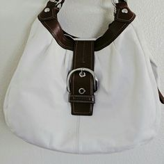 White & brown leather hobo authentic coach White leather with silver hardware and brown trim.Has been used. small scuff at the bottom. And last picture showing some stains, mostly from makeups, that's the bottom inside compartment.  Model # f 15075. Coach Bags Hobos
