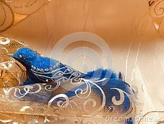 A Christmas blue bird decoration made of glass and feathers rests quietly in shiny cloth.