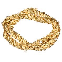 TIFFANY & CO. SCHLUMBERGER Diamond and Gold Bracelet. 18k yellow gold bracelet. It features a unique intertwining gold strands, which create a rope effect. Evenly dispersed in the bracelet are diamonds. Estate