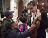 Angela Sulzer gives the children a close look at her violin. <br />(Photo credit: Dana Scherer)
