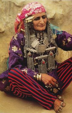 Portrait of an elderly Bedouin woman wearing traditional clothes and jewelry, Yemen