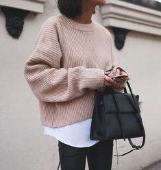 Beige sweater, white shirt, black jeans and bag