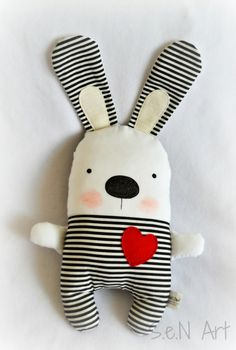 This soft cute handmade black and white striped bunny with red heart is made from 100% cotton fabric and 100% wool felt (heart and the white parts of ears). This fabric bunny plush is stuffed with polyeser filling and is about 28cm high (plus ears). His face is painted with health harmless fabric pen. The same black and white striped fabric on the back. Can be also a unique gift for baby or modern black and white baby nursery decoration. Because of its size it can be used as a pillow (in the…