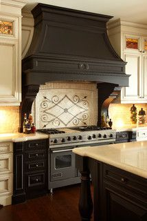 Bitchin' kitchen.... offsetting this commercial stove with black chunky cabinets and a  white backsplash really showcases the fancy hood and turns the whole piece into built in furniture. If you can balance one big focal point like this in a kitchen, you could be more economical on the rest of the cabinetry.